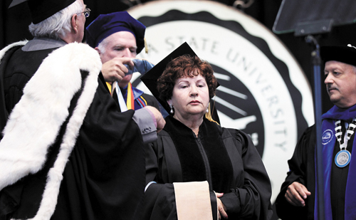 Luz Cardenas being hooded with President Tomás Morales, right, looking on. Photo courtesy of CSUSB