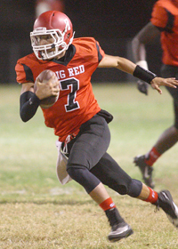 San Bernardino quarterback Sonnyboy Orfiano runs away from Vista del Logo defenders on Friday night during the Cardinals' 43-28 win over the visiting Ravens. Photo by: Robert Attical