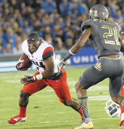 You Forgot Something – Former Rancho Cucamonga star Tahaan Goodman (21) closes in on Terris Jones-Grigsby after losing his helmet in UCLA's 17-7 victory over the Arizona Wildcats on Saturday.