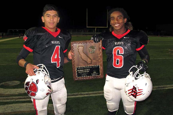 Two Big Cats: REV quarterback Armando Herrera (L) and Malik Lovette pose with the Regional Championship trophy after beating Bakersfield Ridgeview 59-42 in the Regional Finals game on Saturday evening. Photo by: Jon Gaede