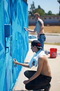Two San Bernardino natives, lead Marc Sellers standing alongside apprentice Jonathan Valadez, create art at Seccombe Lake Park. Photo Credit: Ausencio Fernandez