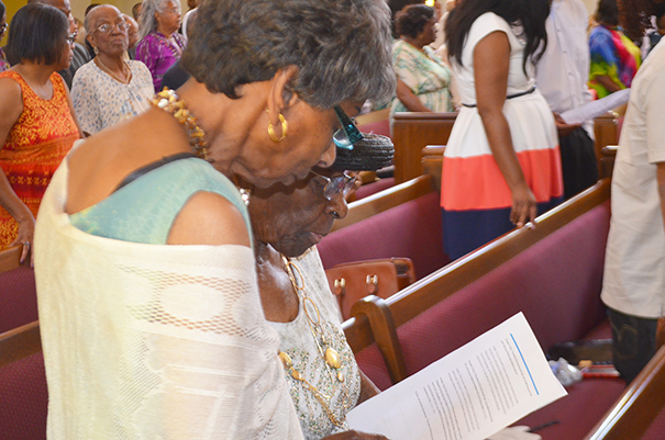 Helen Armstrong, 87, left and Thelma King, 90, both members of the Allen Chapel for decades read along with the rest of the congregation about forgiving Dylann Roof for murdering nine members of Emanuel African Methodist Episcopal Church.