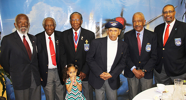 Col. Ralph Smith presented Emeritus Dr. Ruth Jackson, University Librarian and co-founder with a model of the type of flying fortress bomber flown by members of the Tuskegee Airmen during combat operations over Europe in World War II.