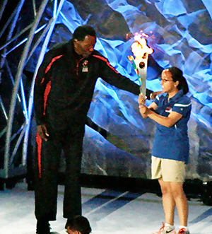 Gold Medal winner Rafer Johnson accepts the Special Olympics torch to light Olympic flame signaling the beginning of the games.