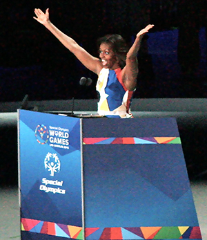 First Lady of the United States Michelle Obama holds up the Special Olympics symbol as she officially opens the games.