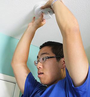 Volunteer Chris Chung tests a newly-installed smoke alarm during an American Red Cross Home Fire install event held in the Airport Neighborhood of Riverside.