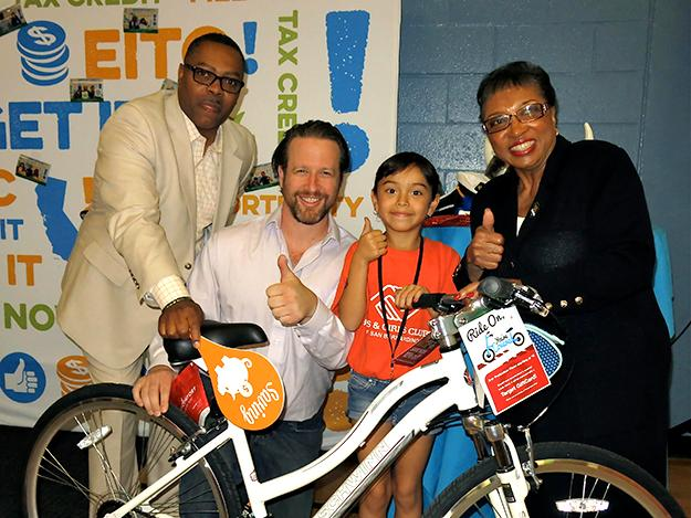 A happy Boys & Girls Club member with her new bike is joined by A. Majadi, Joe Sanberg, and Assembly member Cheryl Brown.