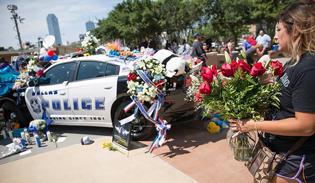 A woman places flowers at a memorial outside the Dallas Police Headquarters